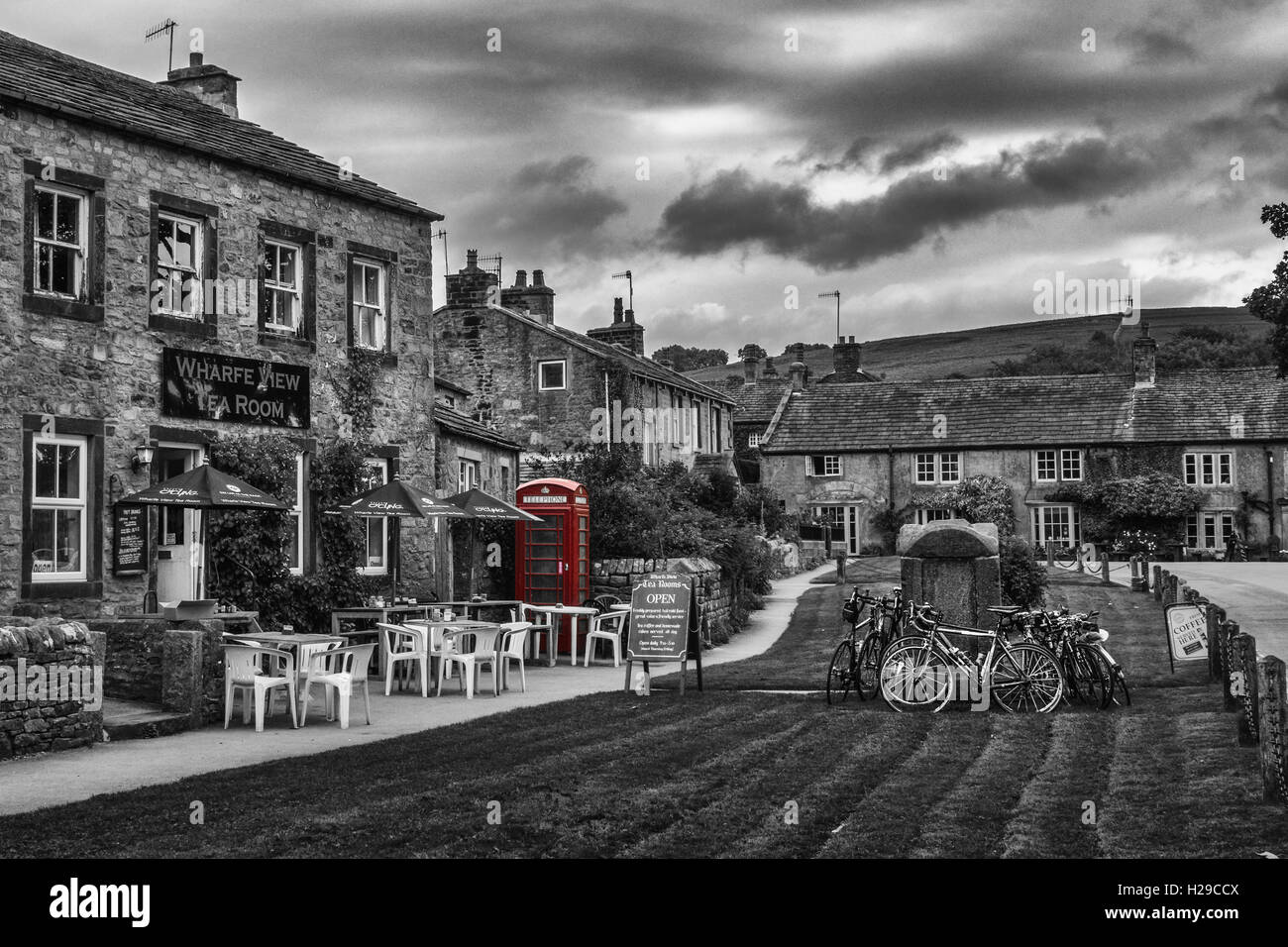 Black and white landscapes: Burnsall village with a traditional red telephone box, North Yorkshire, England, UK - Stock Image
