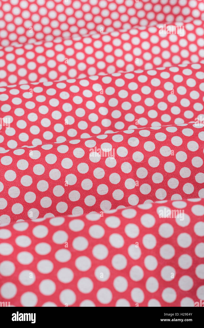 Abstract folds of red-white polka dot cotton material. Concept 'International Dot Day' and perhaps a dotty - Stock Image