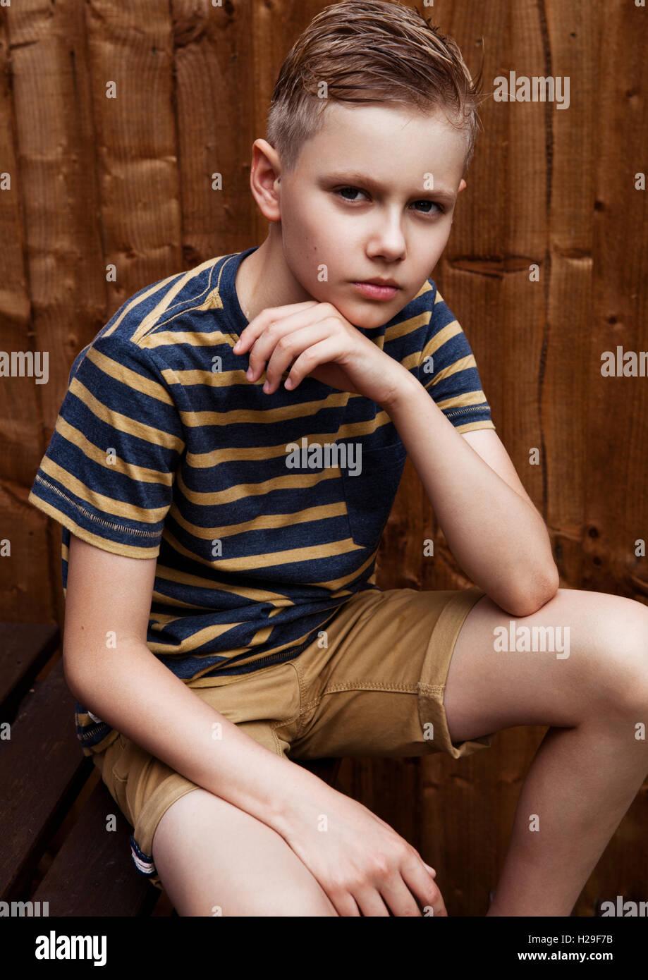 Portrait of handsome teenage happy boy outdoor in backyard.Brown wood  background - Stock Image
