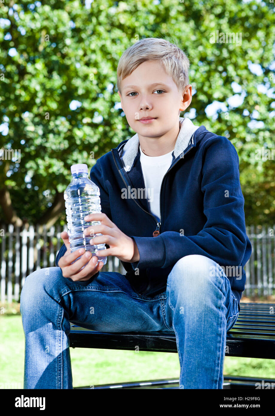 Young teenage boy with bottle of water in park sitting on the bench Stock Photo