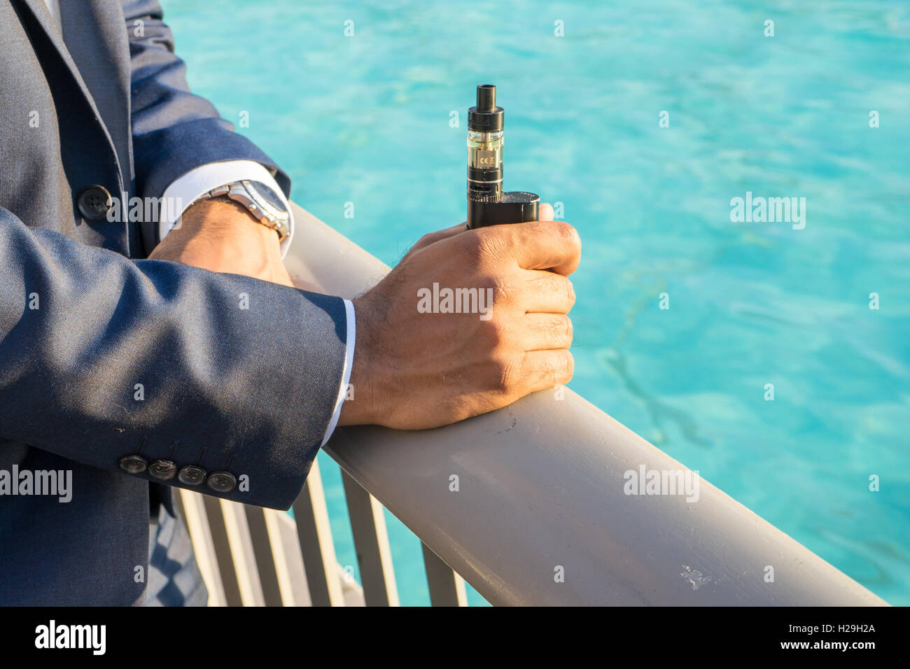 An asian male holds an electronic cigarette also known as an E-Cig - Stock Image