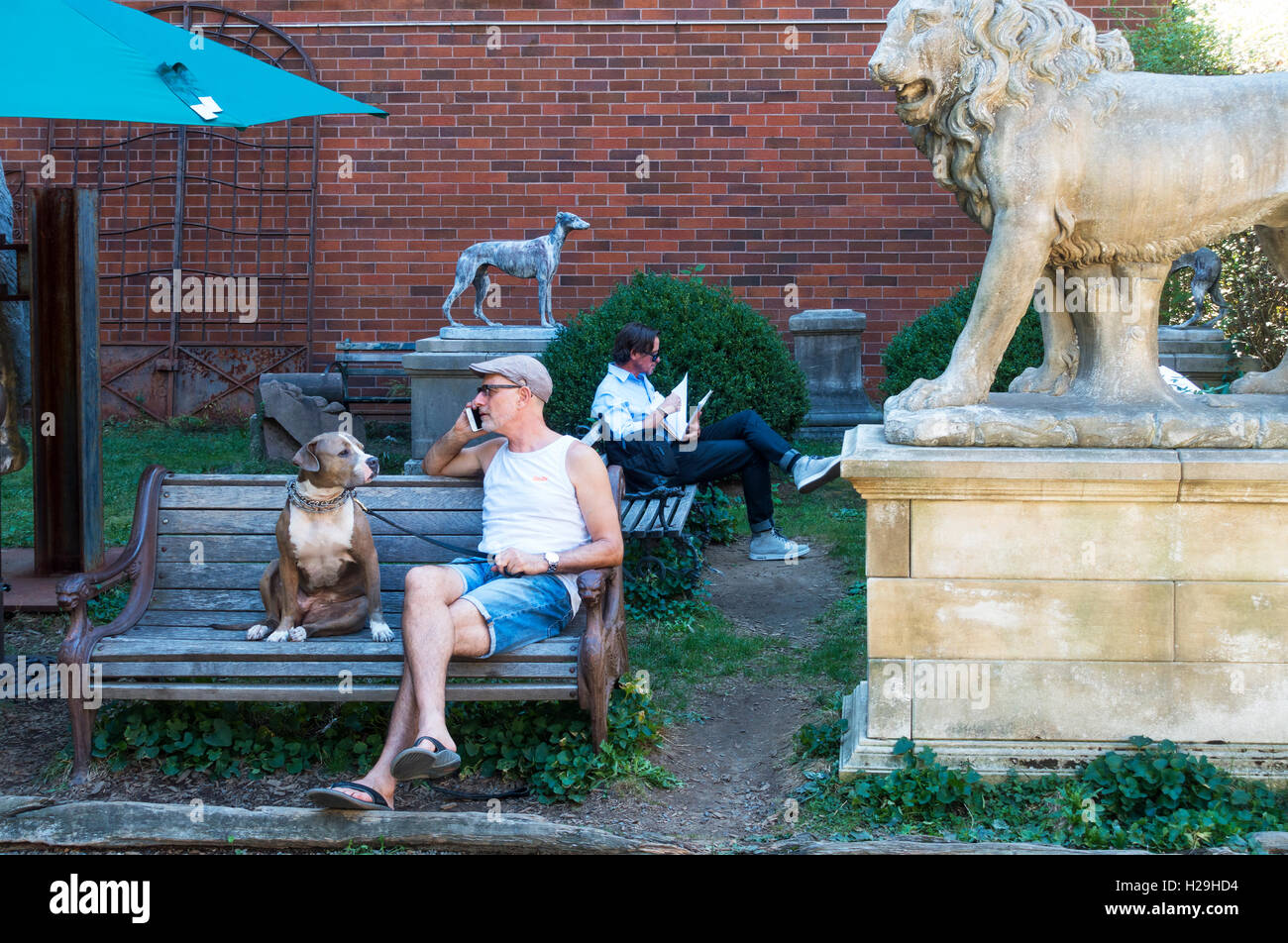 Senior man with his pit bull dog relaxing in Elizabeth Street Garden in Nolita - Stock Image