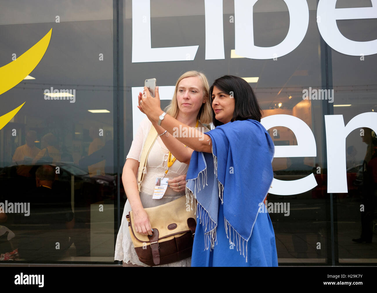 Delegates at the Liberal Democrats party conference in Brighton 2016 taking a selfie in front of the party logo. - Stock Image