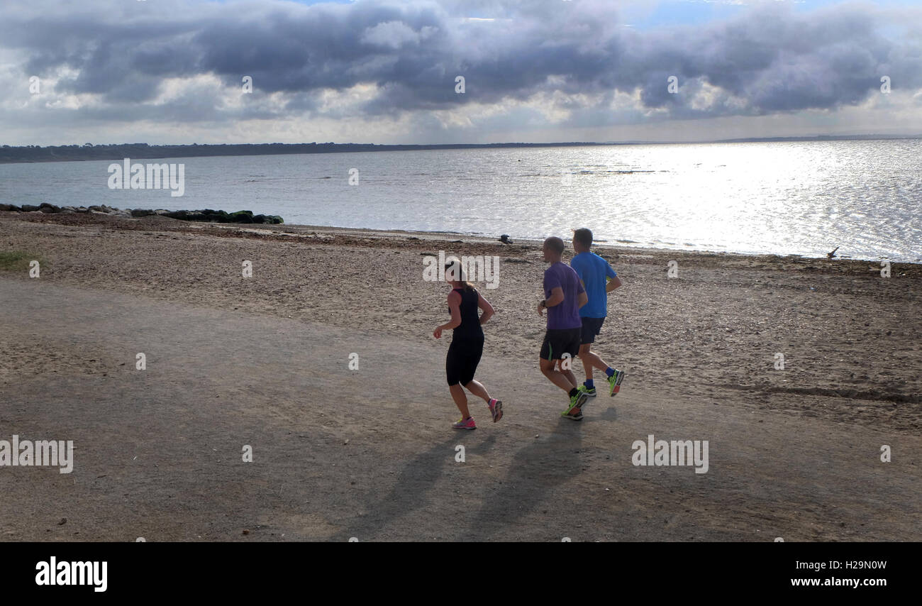 Runners- jogging along the seafront, Mudeford beach, near Christchurch, Dorset. - Stock Image