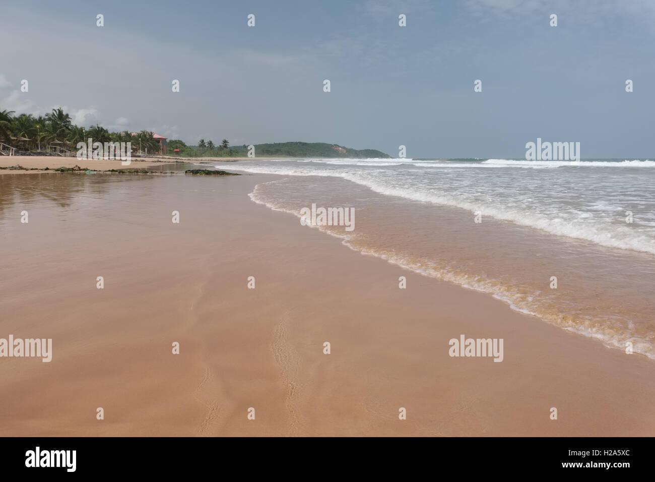Deserted undeveloped golden sandy beach at Busua Beach in Ghana - Stock Image