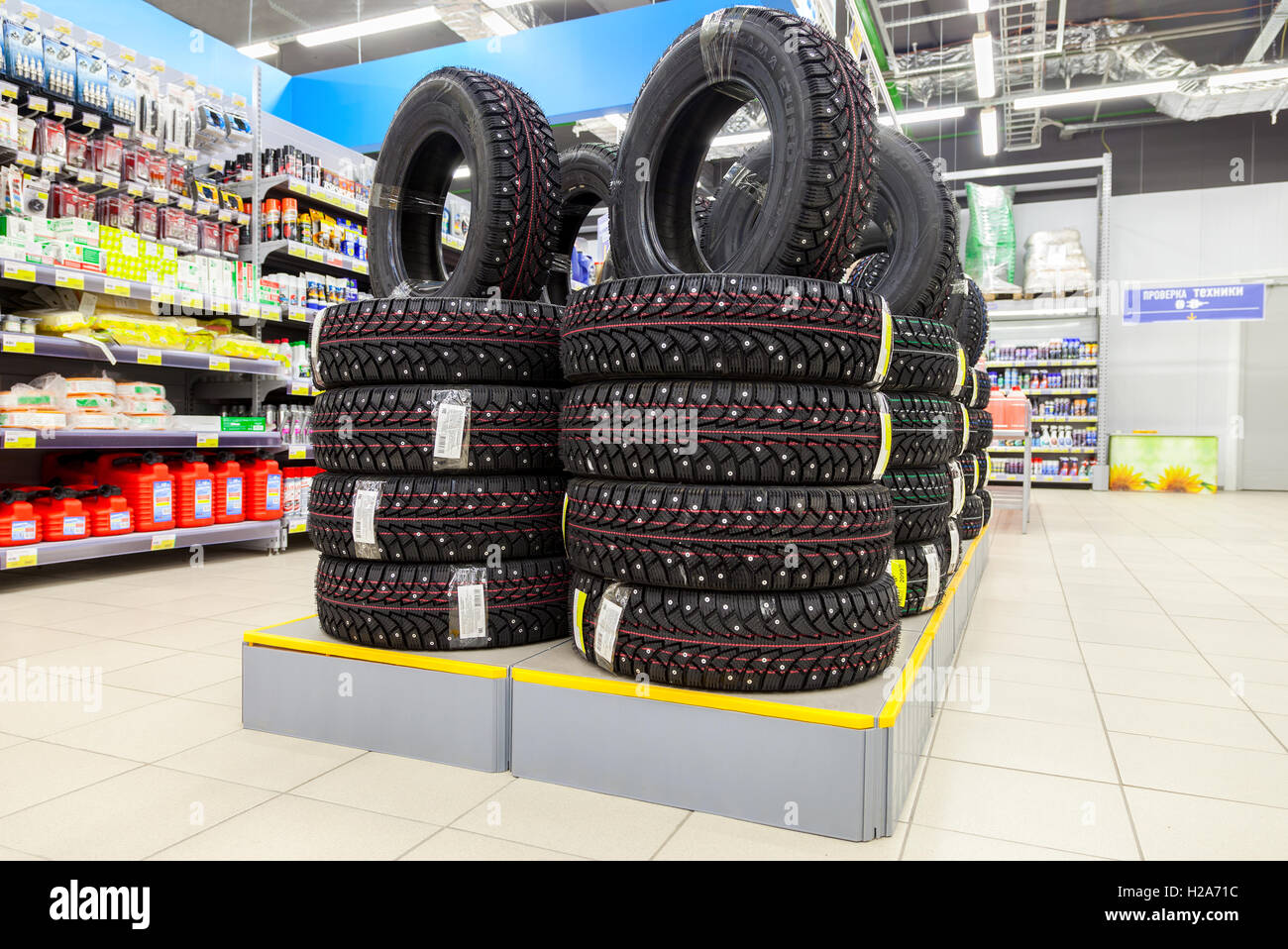 Brand new winter tires stacked up for sale in the hypermarket Lenta - Stock Image