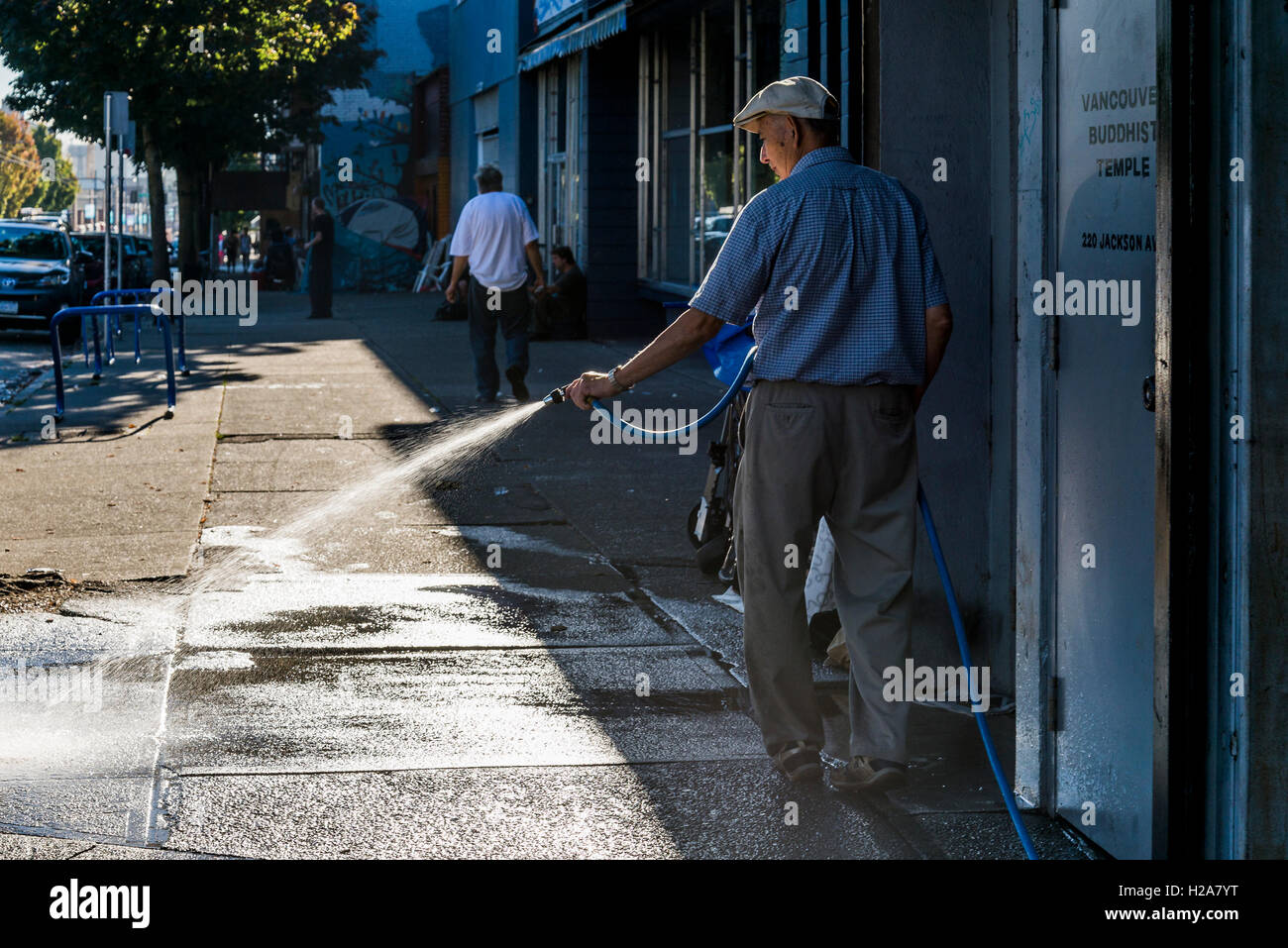 Man cleaning sidewalk with hose, Downtown Eastside, Vancouver, British Columbia, Canada - Stock Image