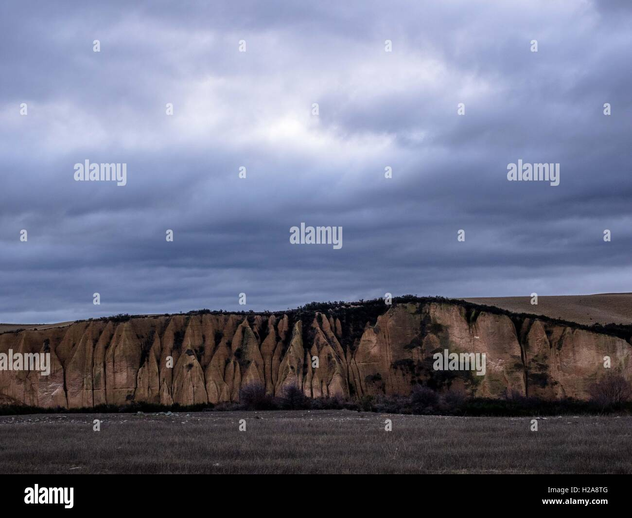 dusk looking over grey fields toward  sluiced cliff a big rolling sky beyond kyeburn diggings, historic gold field - Stock Image