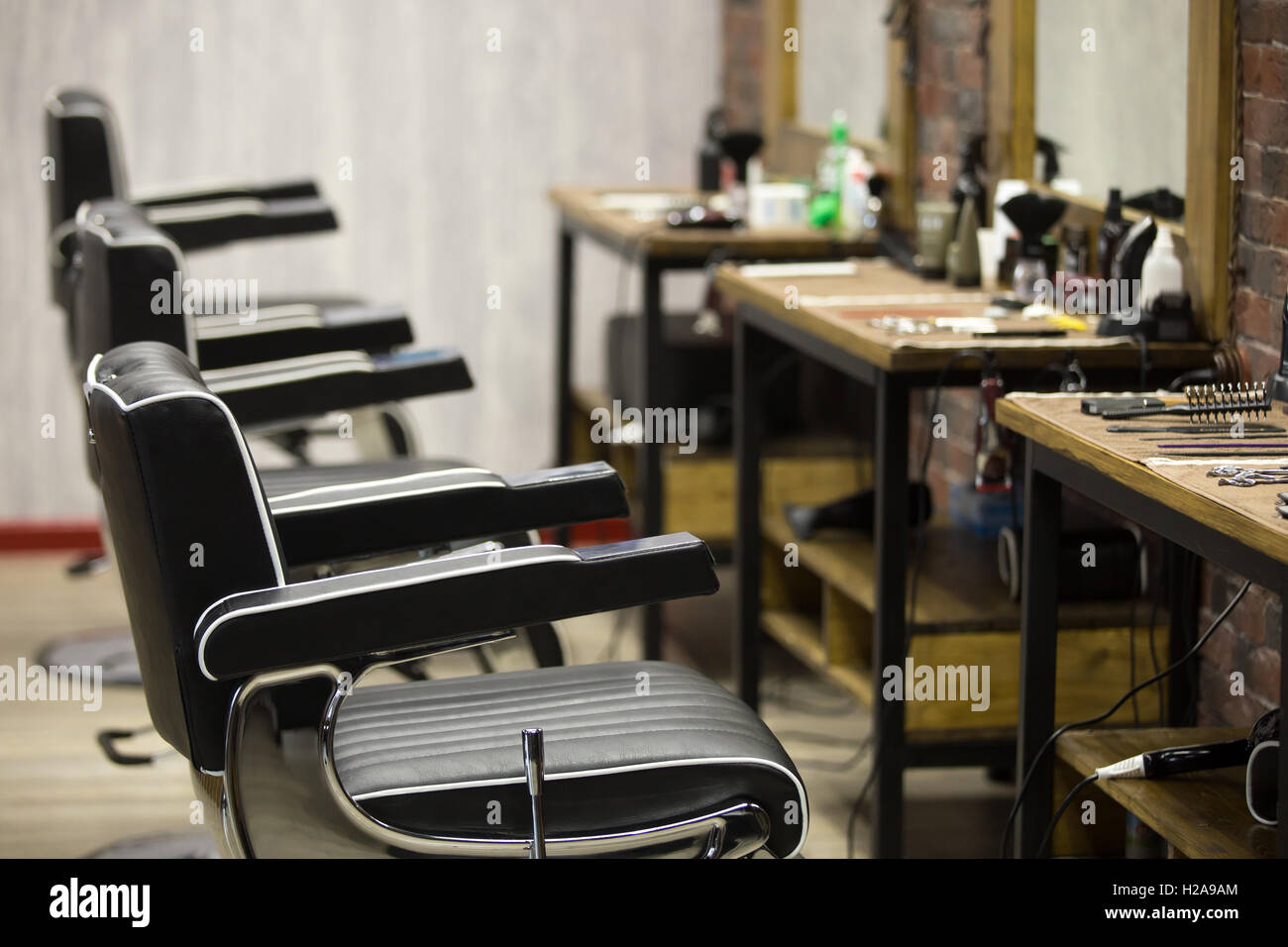 Row Of Black Leather Chairs In Modern Barber Shop Interior. Horizontal  Indoors Shot