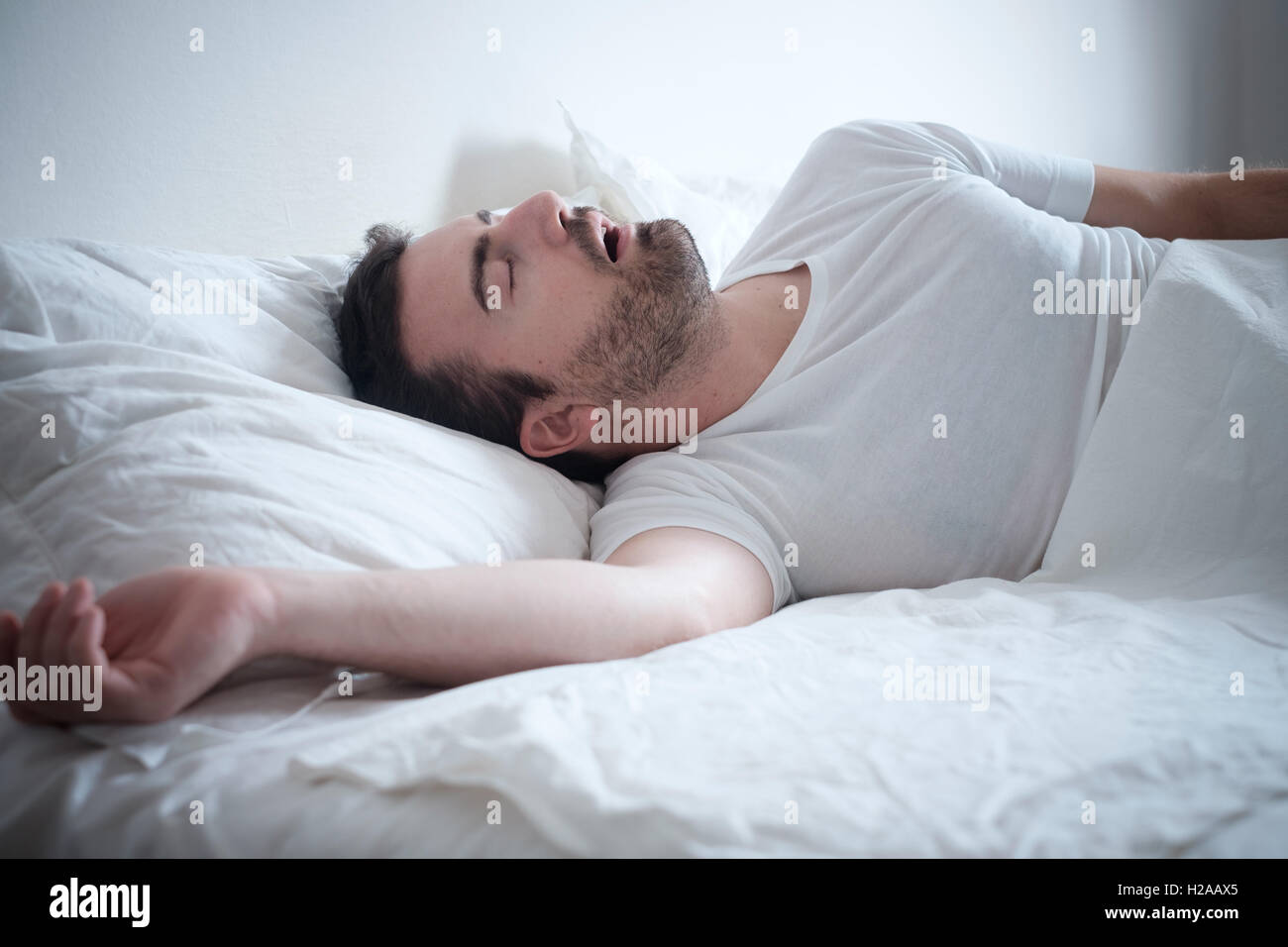 Man sleeping in his bed and snoring loudly - Stock Image