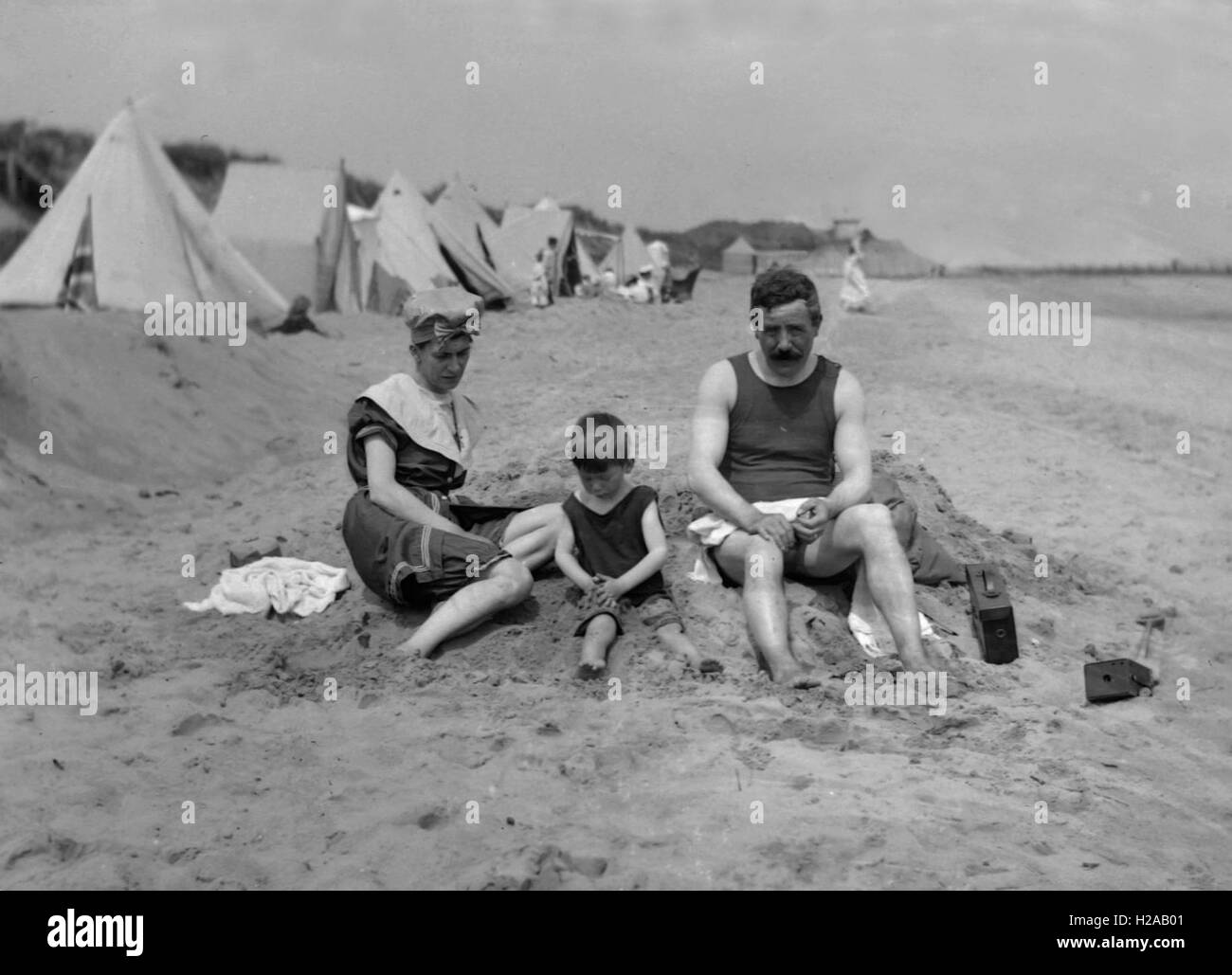 Couple and child playing on the beach at the seaside in bathing costumes. Note the Box Brownie Camera to the right - Stock Image