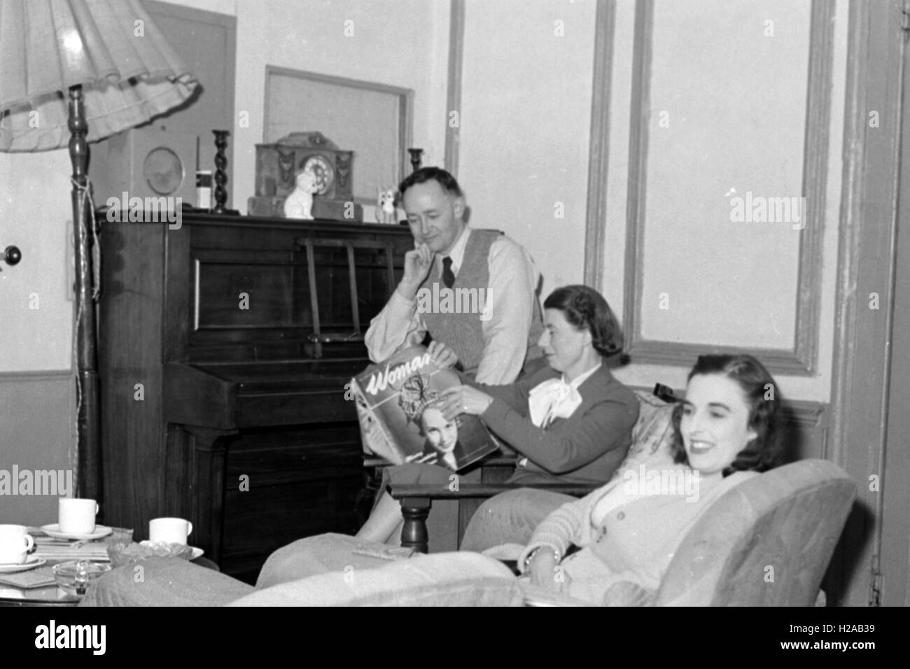 Typical family living room c1950. Mother is reading 'Woman Magazine'. Photo by Tony Henshaw - Stock Image