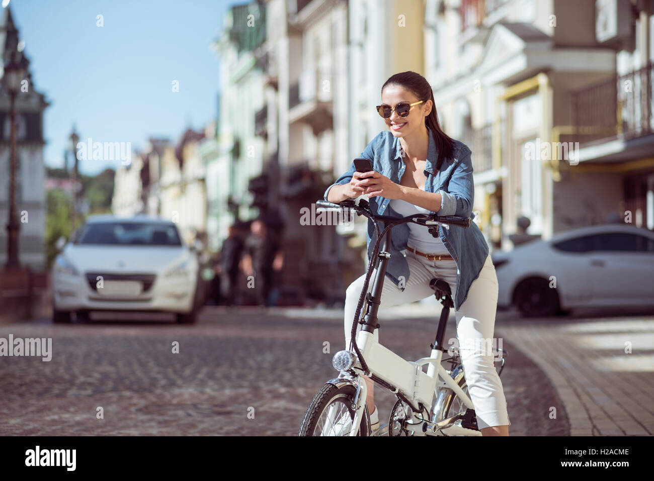 Positive woman riding a bicycle - Stock Image