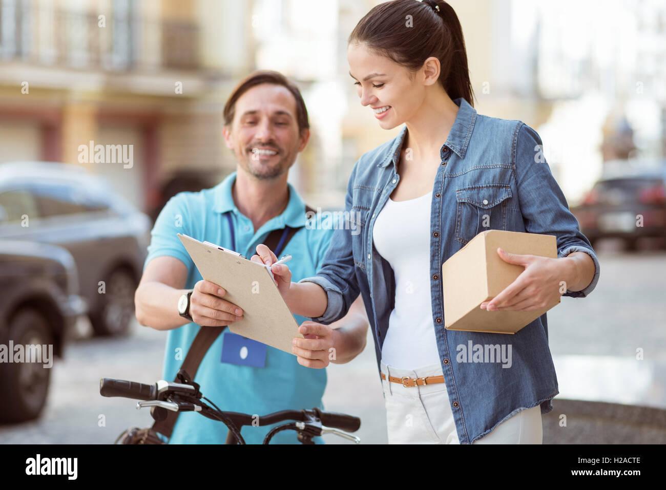 Joyful professional courier delivering parcel - Stock Image