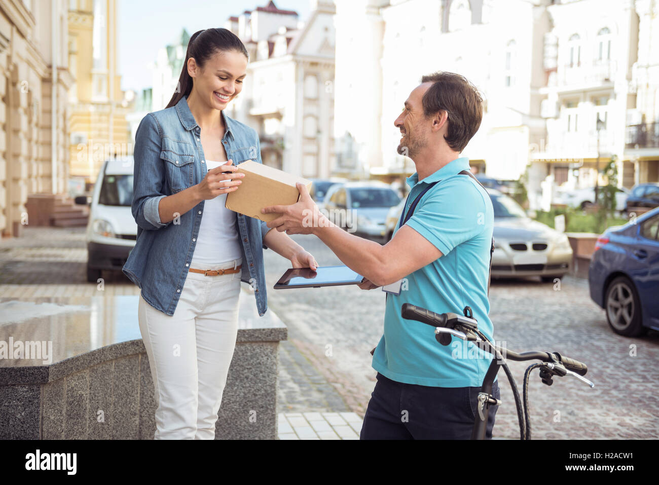 Cheerful courier delivering parcel to the client. - Stock Image