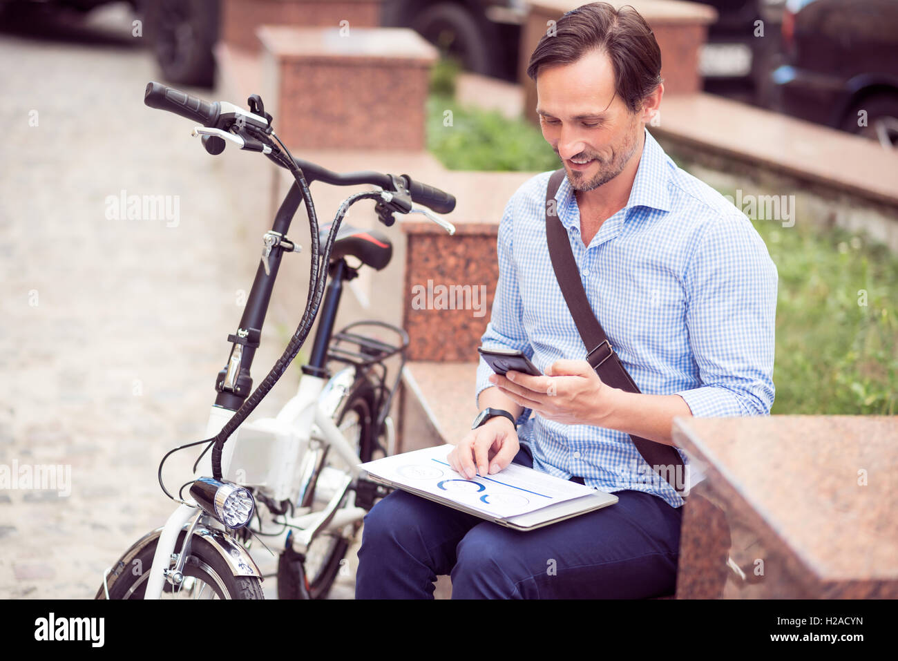Pleasant smiling man sitting in the street - Stock Image