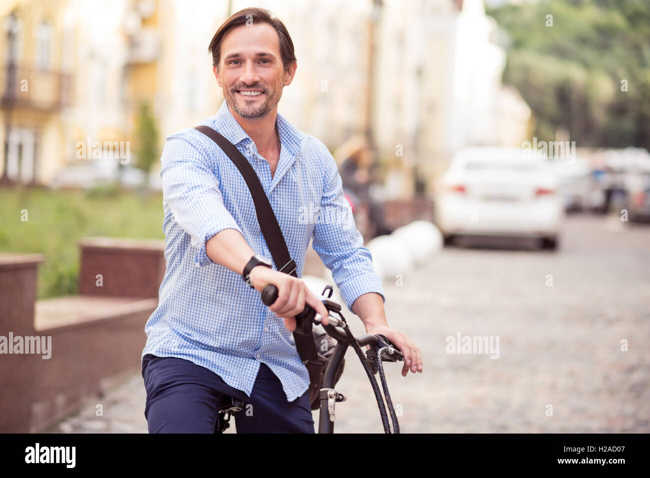 Cheerful man riding a bike - Stock Image