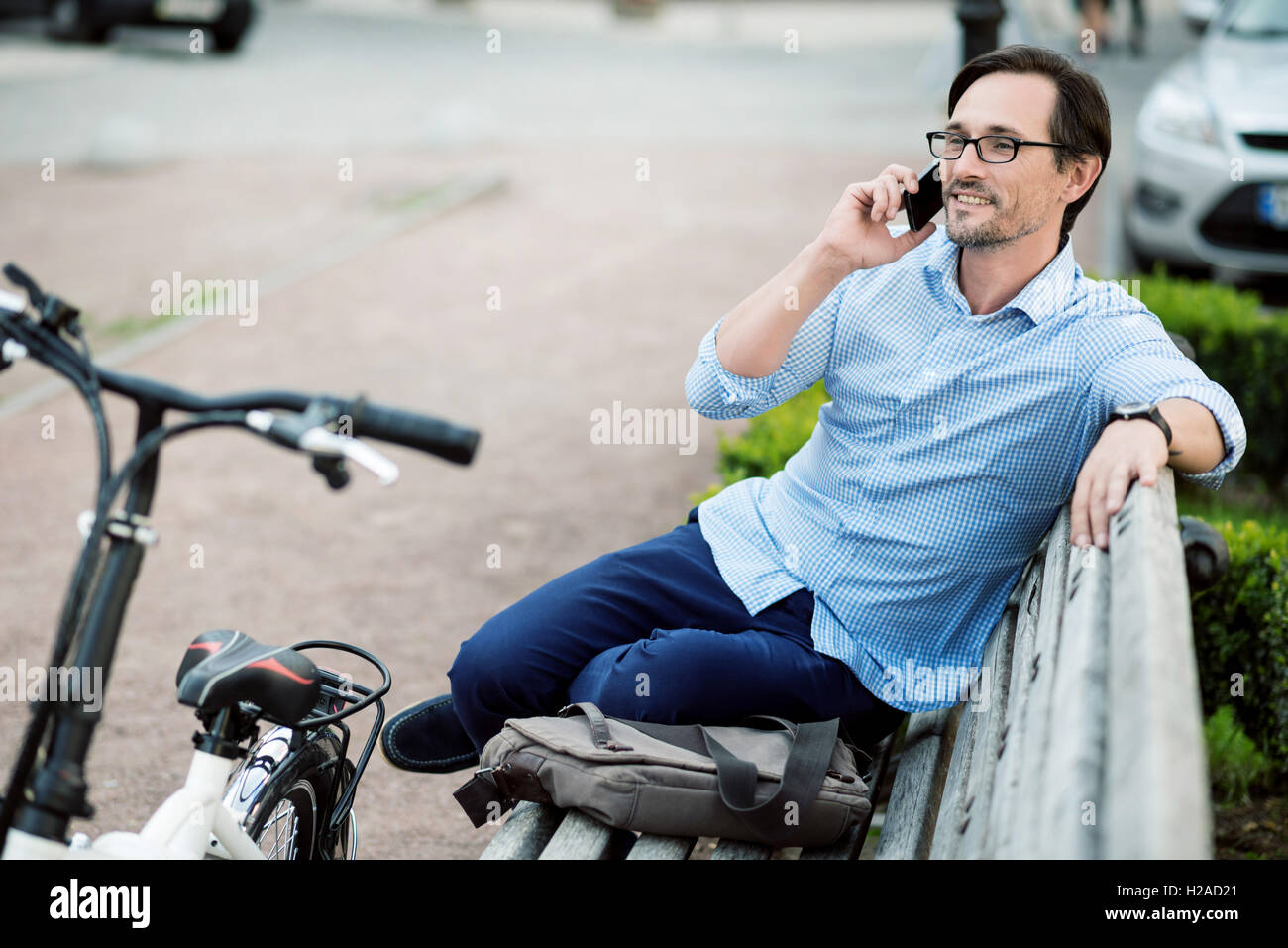 Relaxed bespectacled man speaking on cellphone. - Stock Image