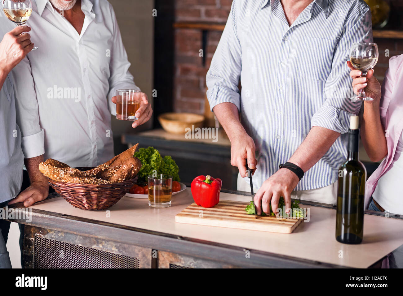 Happy family cooking together in kitchen during reunion - Stock Image
