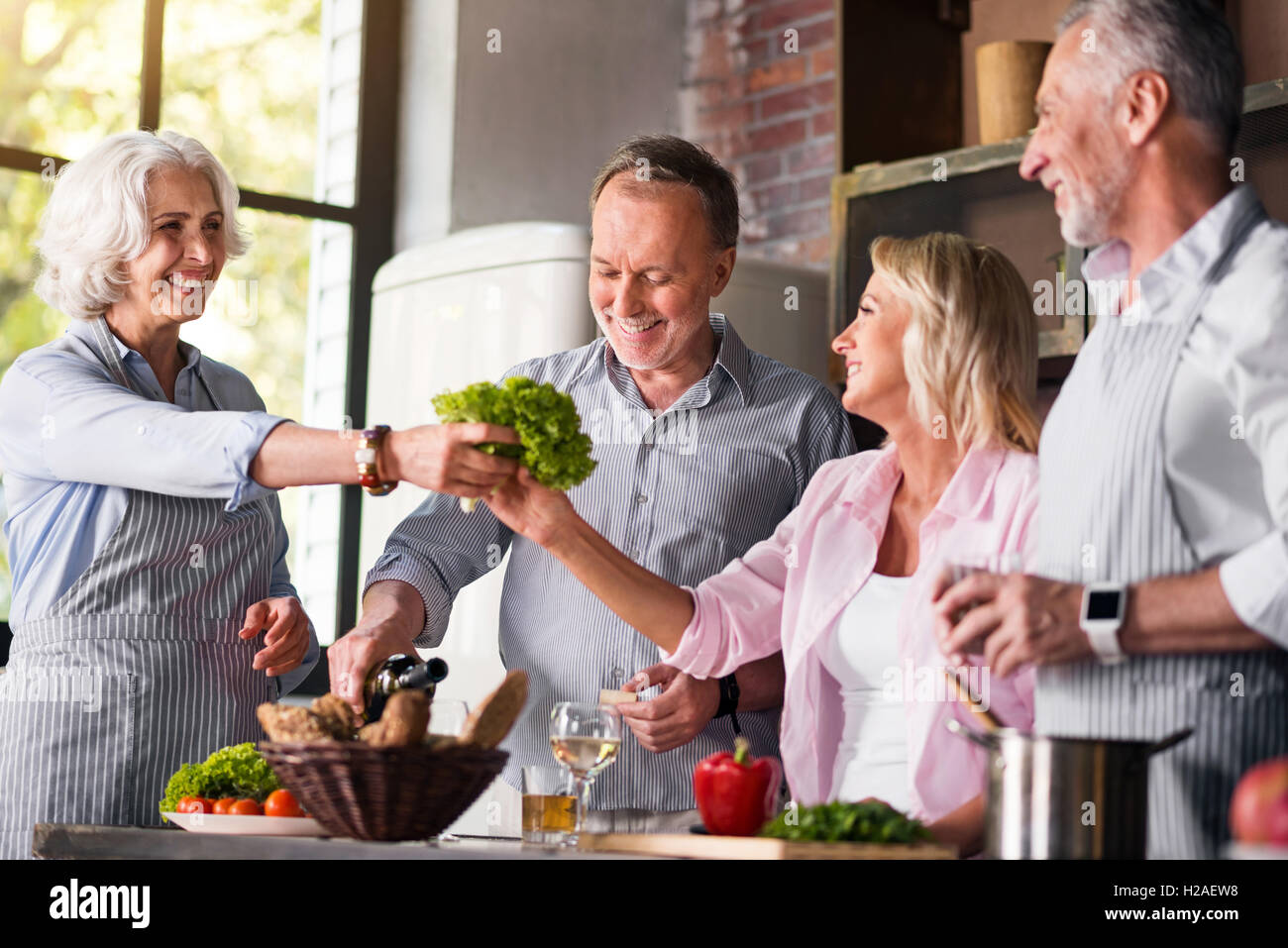 Joyful family cooking dinner all together in the kitchen - Stock Image