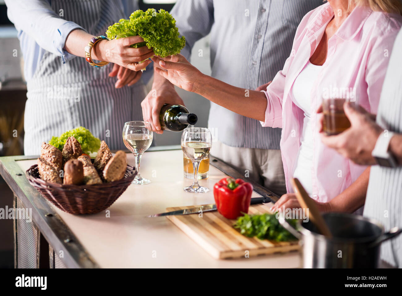 Family cooking food together while enjoying wine - Stock Image