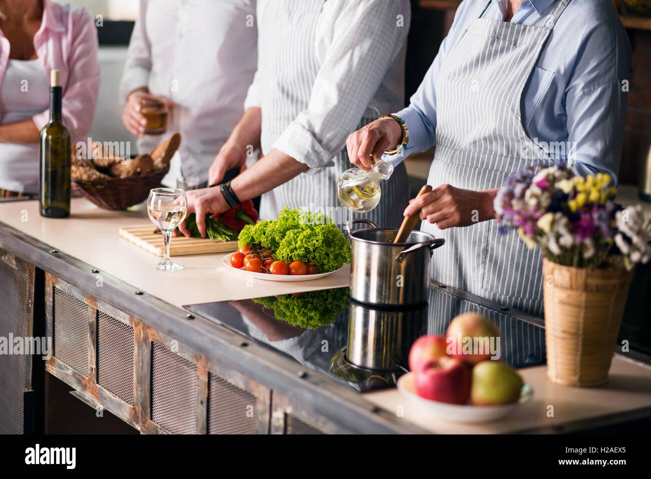 Family and friends cooking food at dinner table - Stock Image