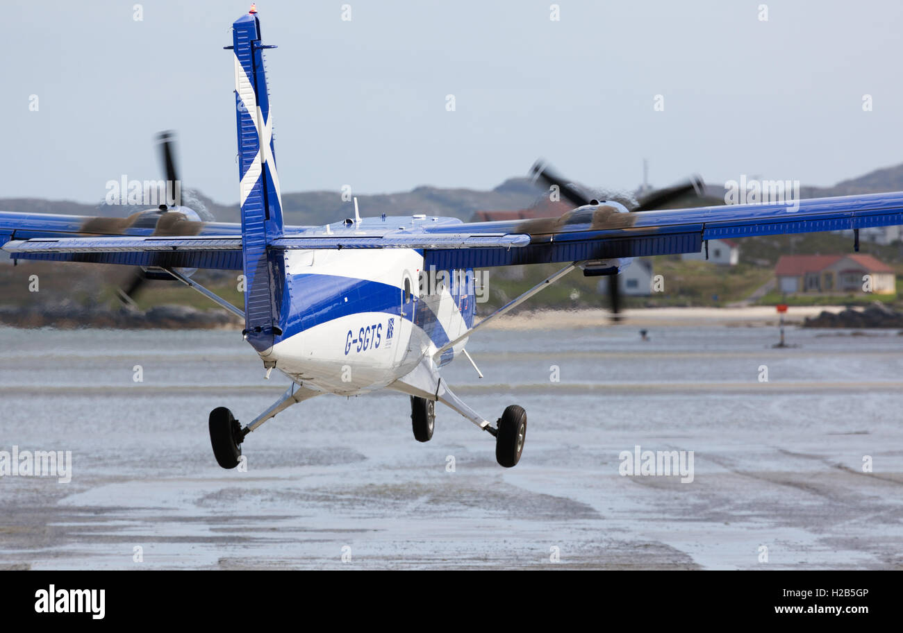 Barra, Outer Hebrides, Scotland G-SGTS - Viking DH-6-400 Twin Otter - Loganair aircraft landing at Barra Airport. - Stock Image