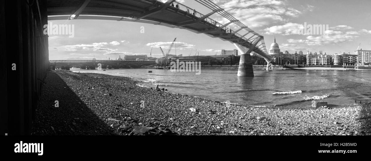 Thames Bankside next to the Millenium Bridge shot in monochrome and wide angle looking north towards St Pauls - Stock Image