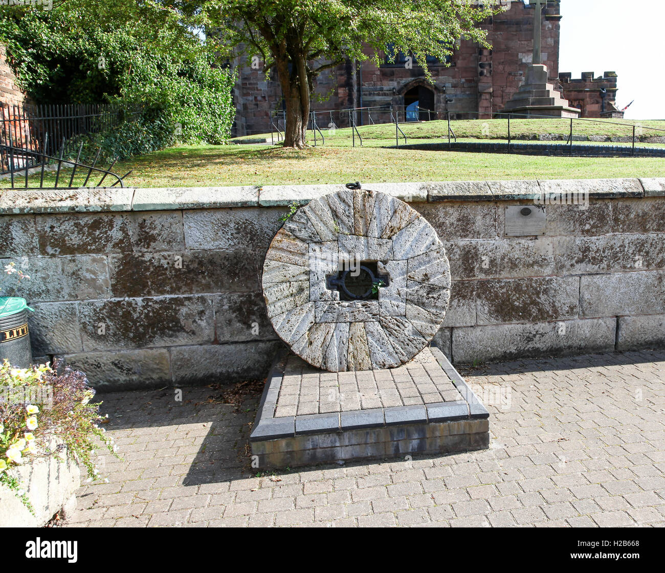 A mill stone in the street in the village of Audlem Cheshire England UK - Stock Image