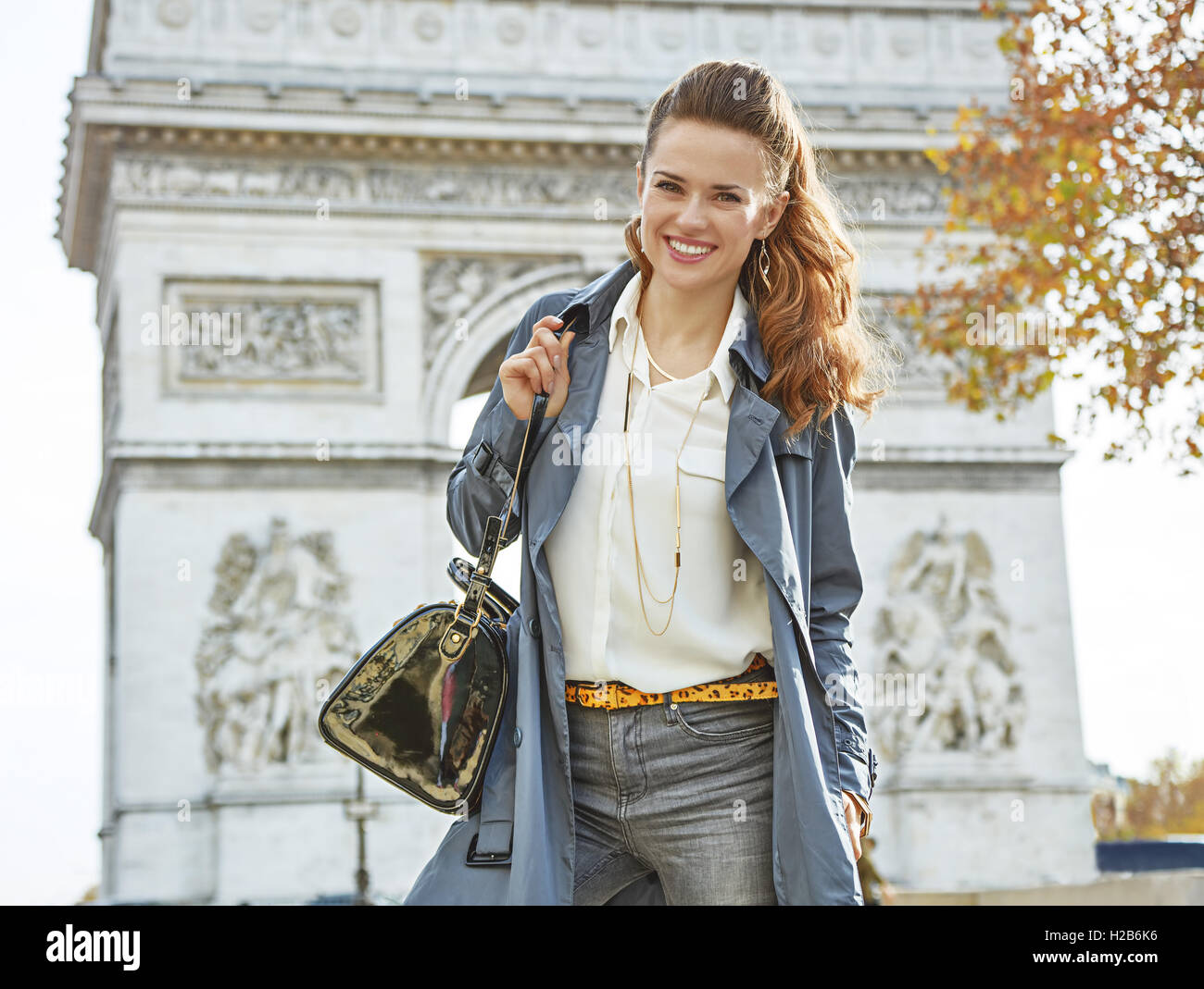 Stylish autumn in Paris. Portrait of happy young elegant woman in trench coat in Paris, France - Stock Image