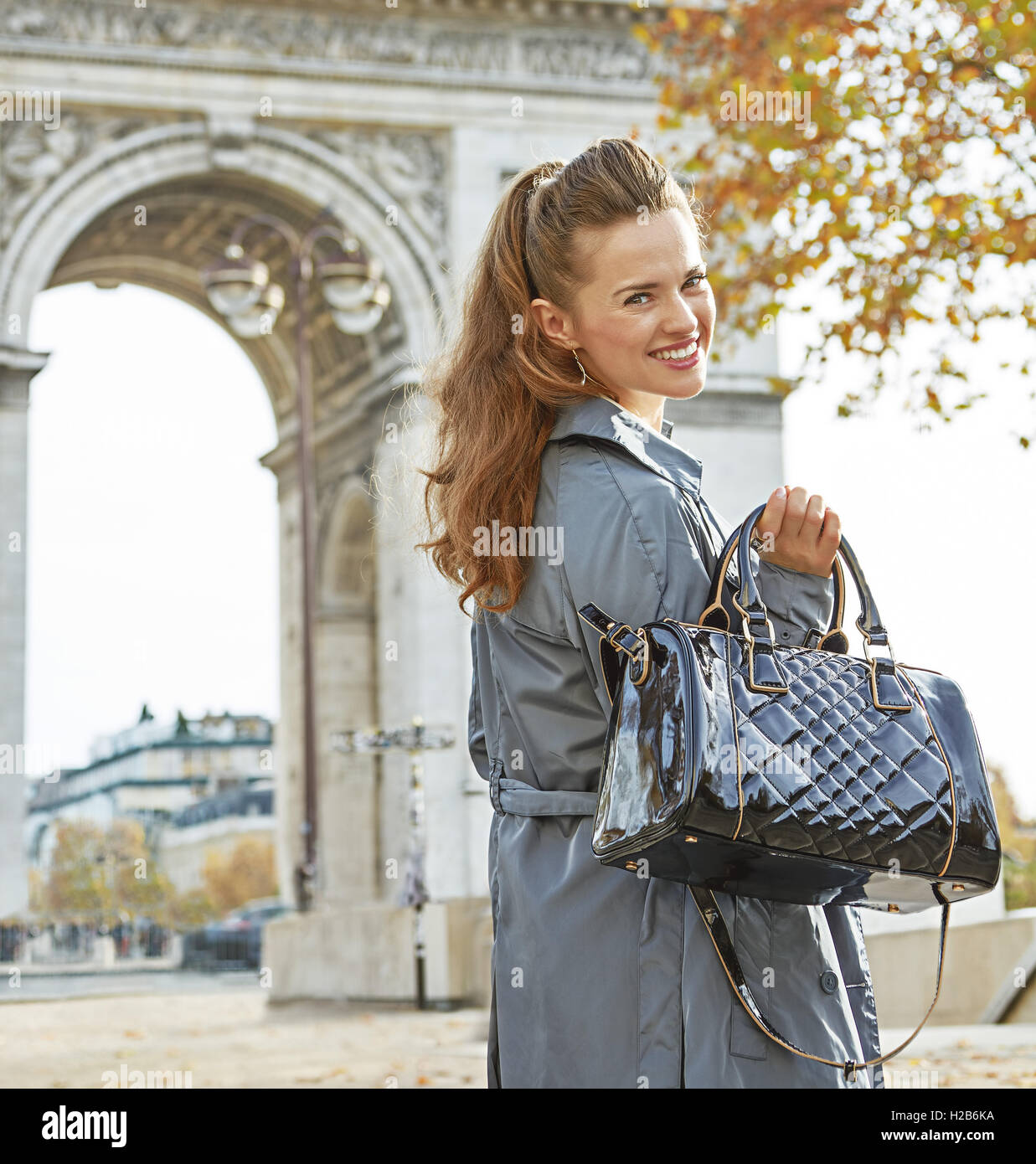 Stylish autumn in Paris. Portrait of happy young fashion-monger in trench coat in Paris, France - Stock Image