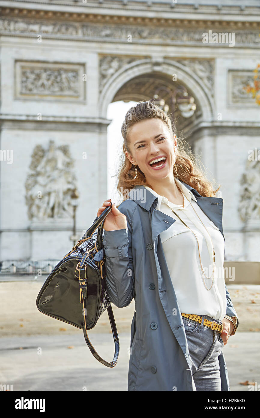 Stylish autumn in Paris. Portrait of smiling young fashion-monger in trench coat in Paris, France - Stock Image