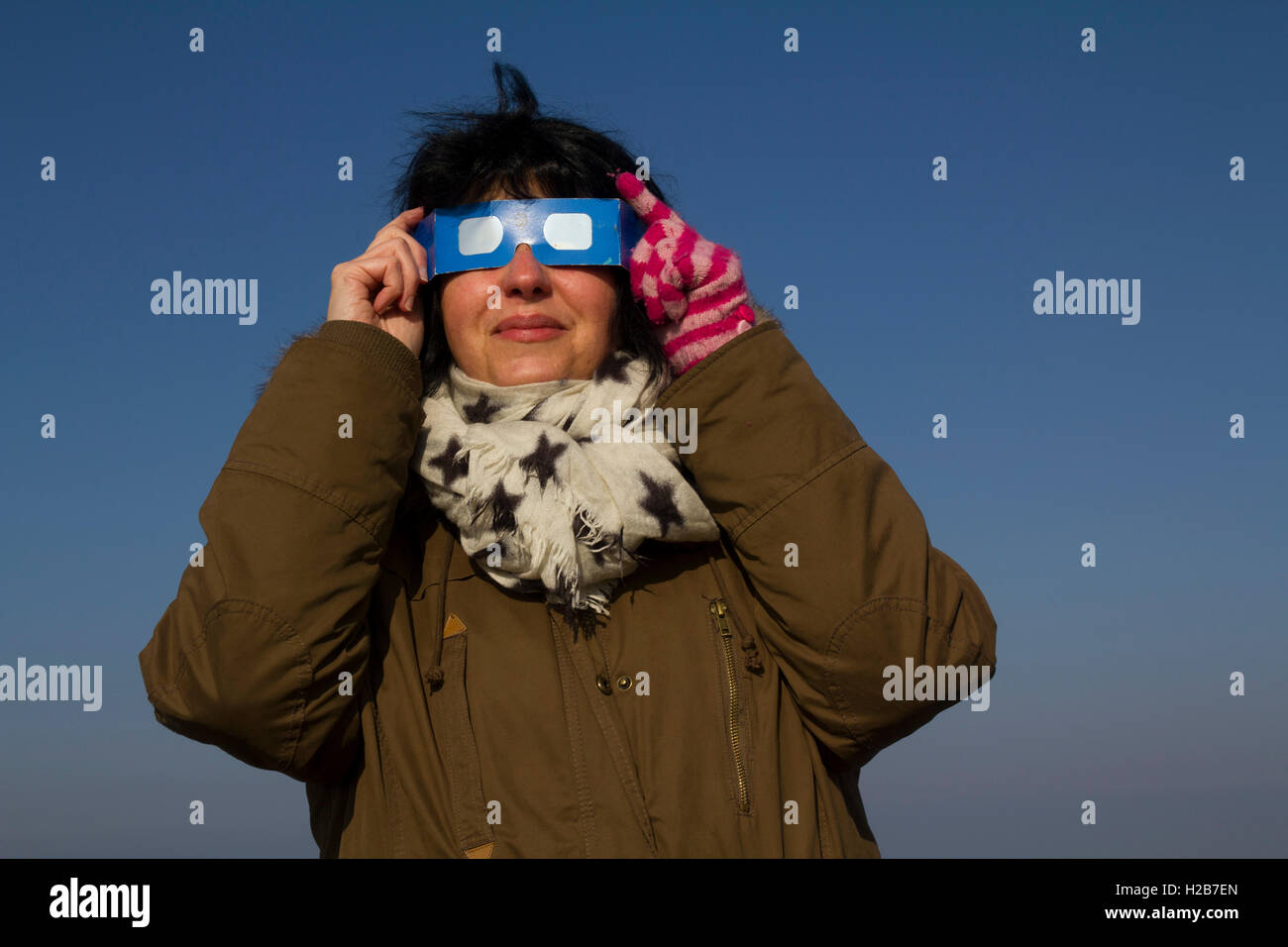 Woman with safety glasses to watch the spectacular partial solar eclipse, 20th Mar, 2015, Gower Peninsular, Wales, Stock Photo