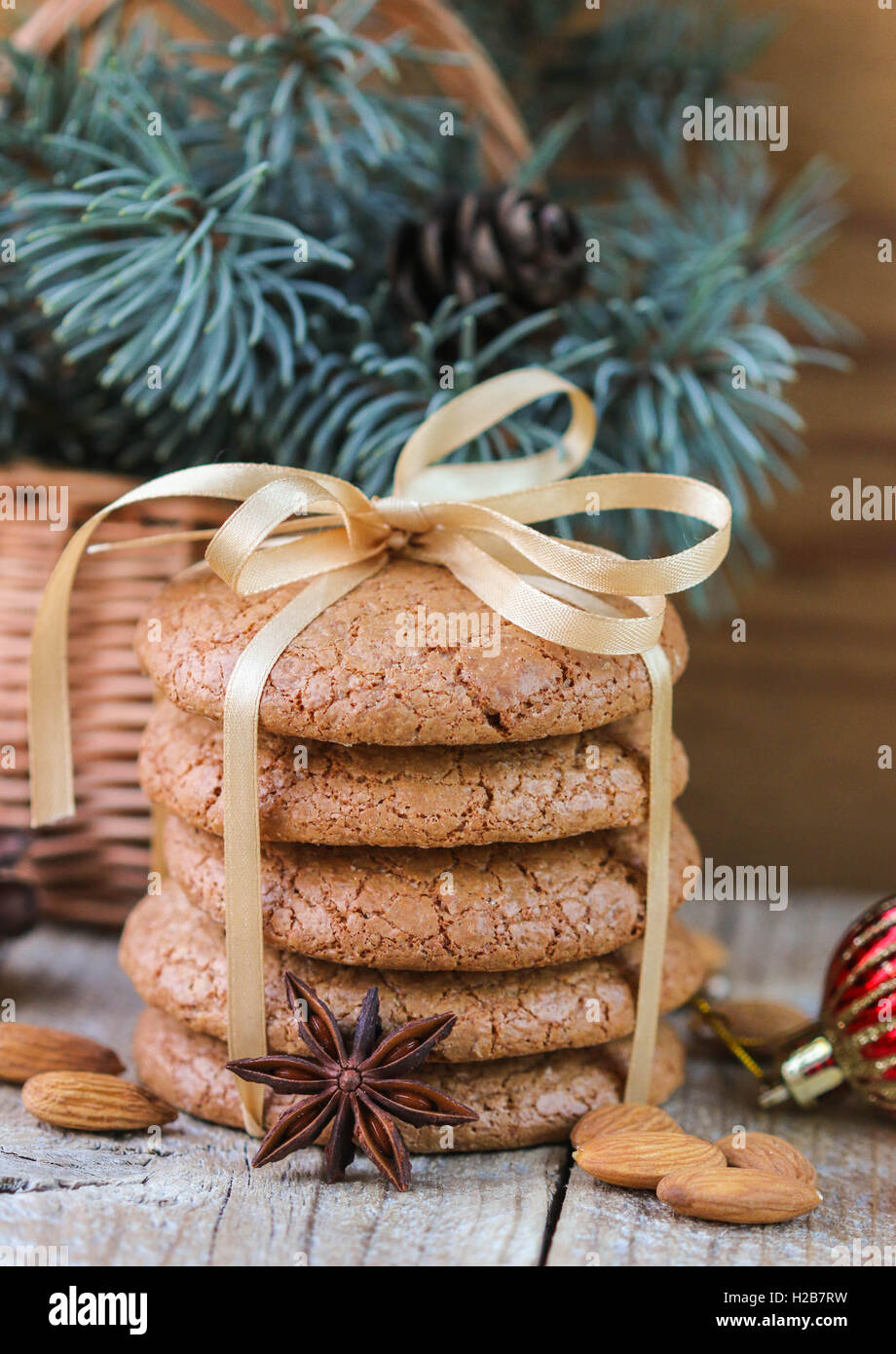 Spiced cookies with almonds. Christmas gifts. Round cookies, tied with ribbon and spruce branch in a basket on the - Stock Image
