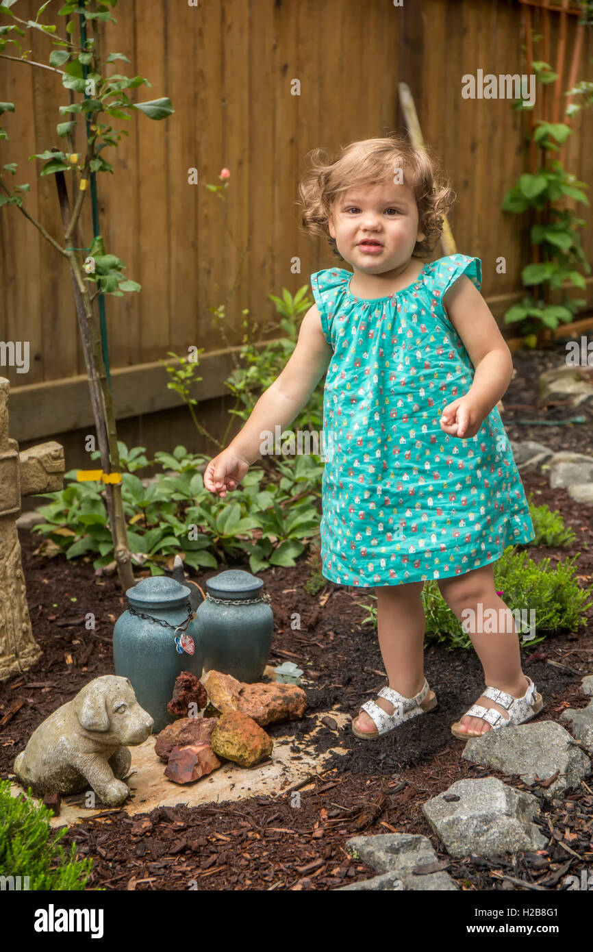 Eighteen month old girl walking outside in a garden where there are urns of ashes from pet dogs, in Issaquah, Washington, Stock Photo