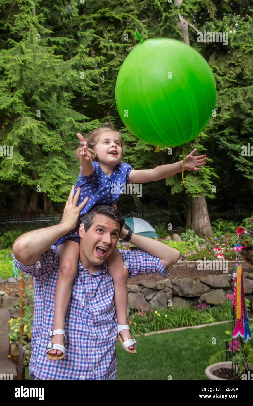Thirty-four year old father holding his three year old daughter as she catches a balloon tossed to her - Stock Image