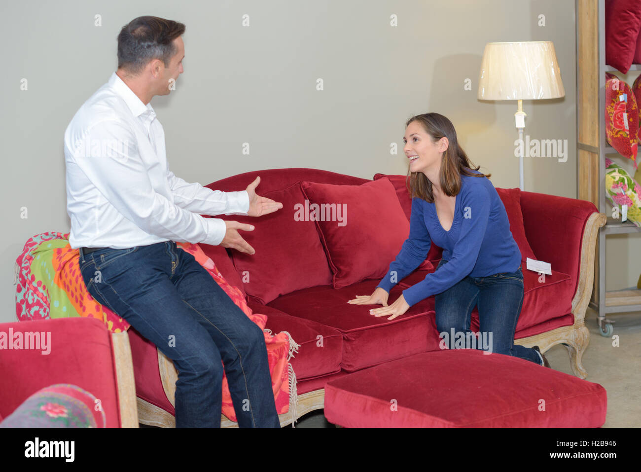 Woman inviting man to test sofa with her Stock Photo