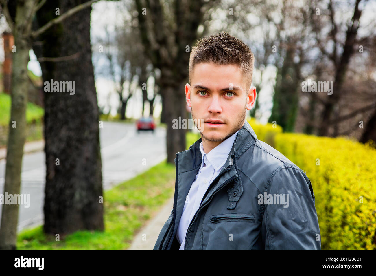 Portrait of handsome young man looking to a side while sitting in city park - Stock Image