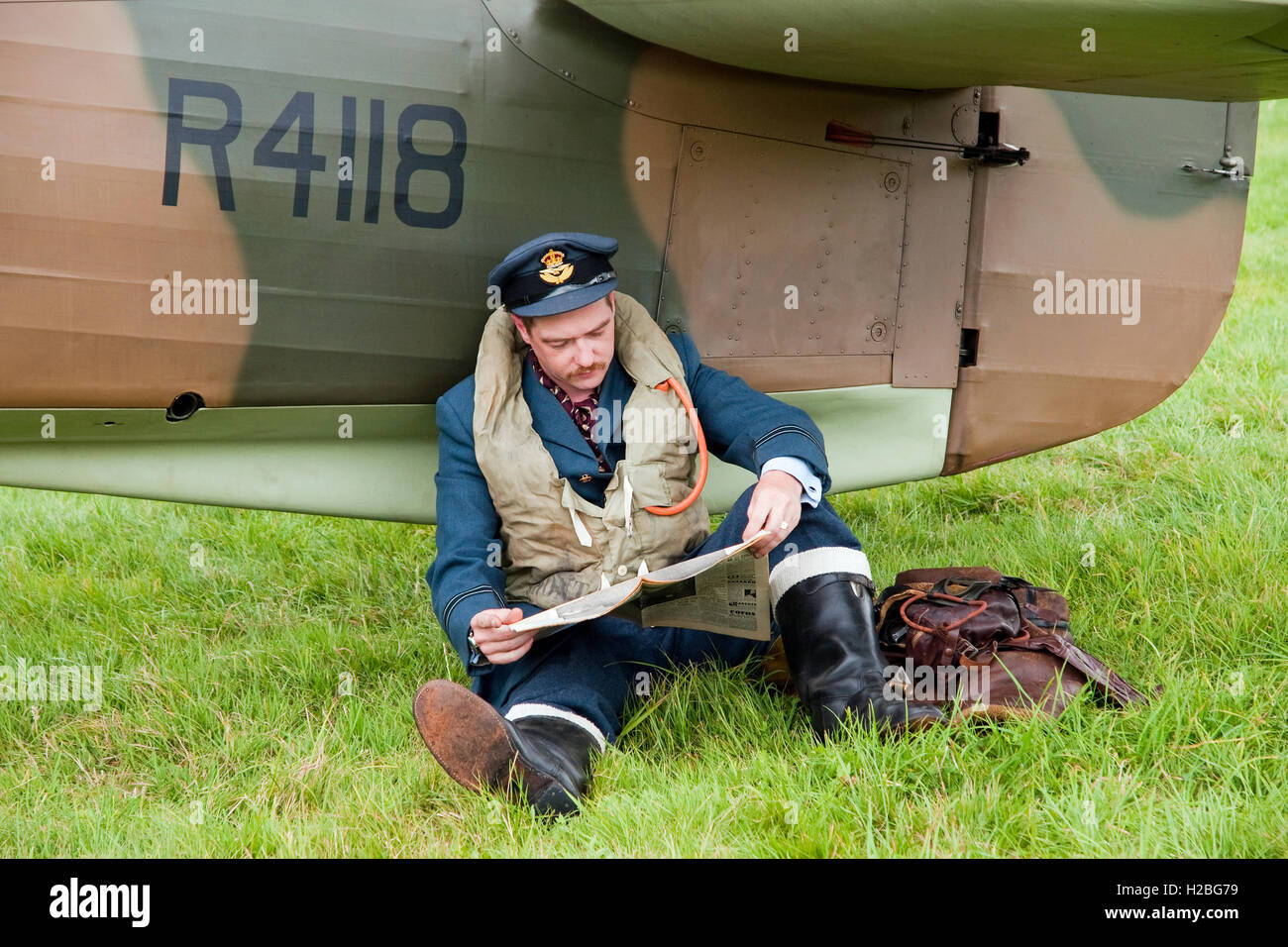 Re-Enactor dressed as a Battle of Britain pilot 'waits for a scramble' with his Hawker Hurricane fighter - Stock Image