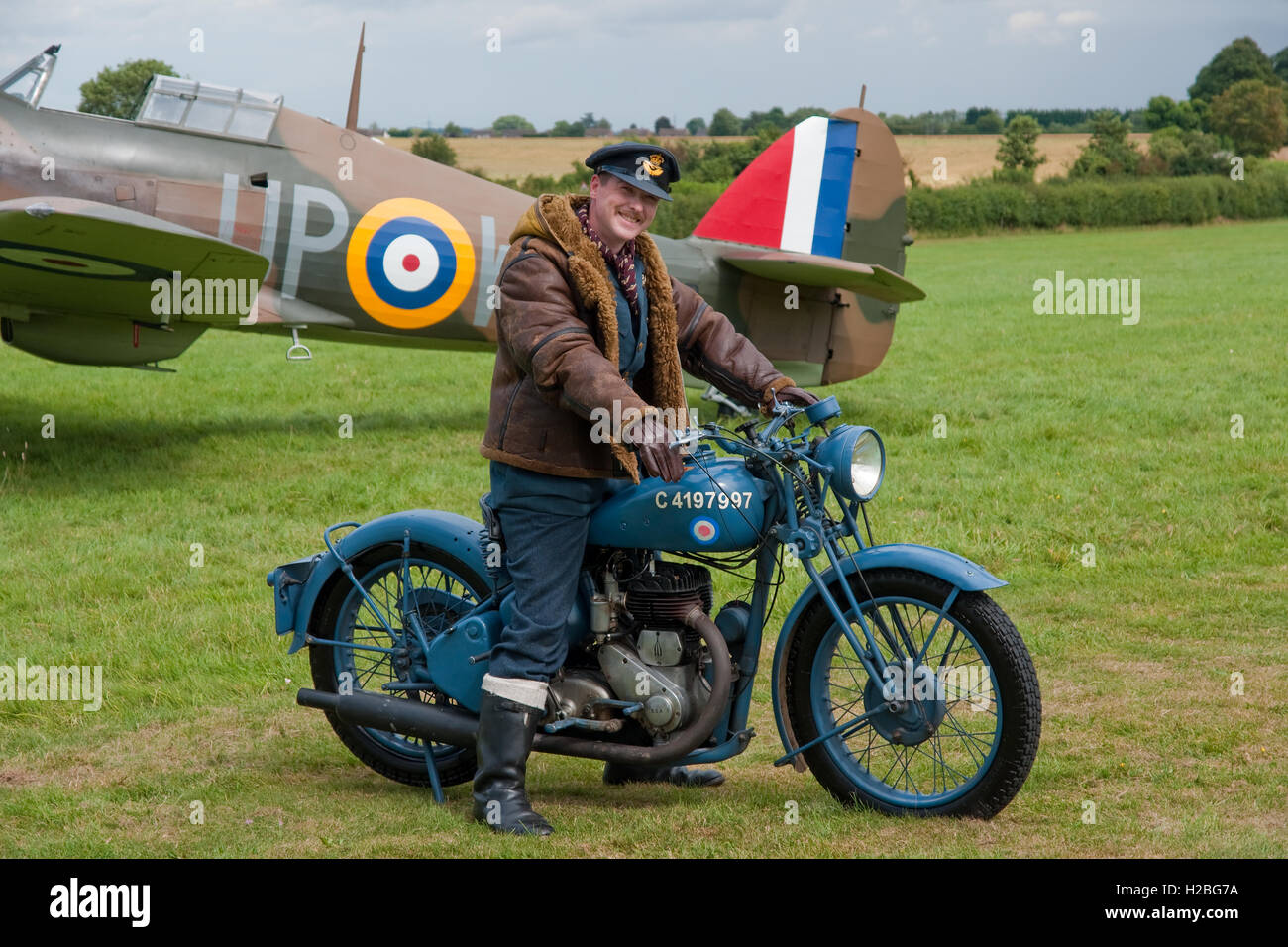 Re-Enactor dressed as a Battle of Britain pilot posed with a Hawker Hurricane fighter and a period-authentic RAF - Stock Image
