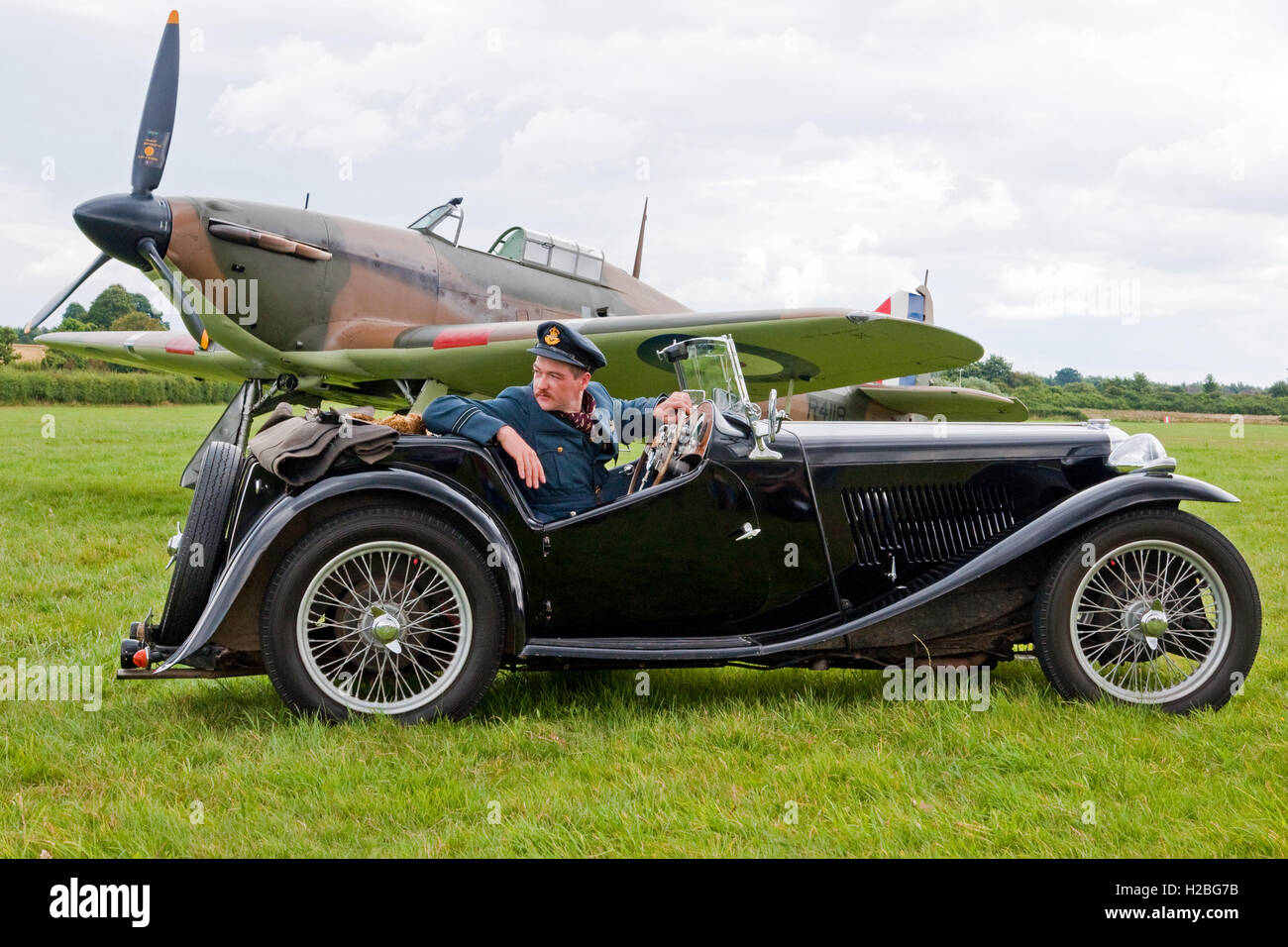Re-Enactor dressed as a Battle of Britain pilot posed in a period-authentic MG sports car and a Hawker Hurricane - Stock Image