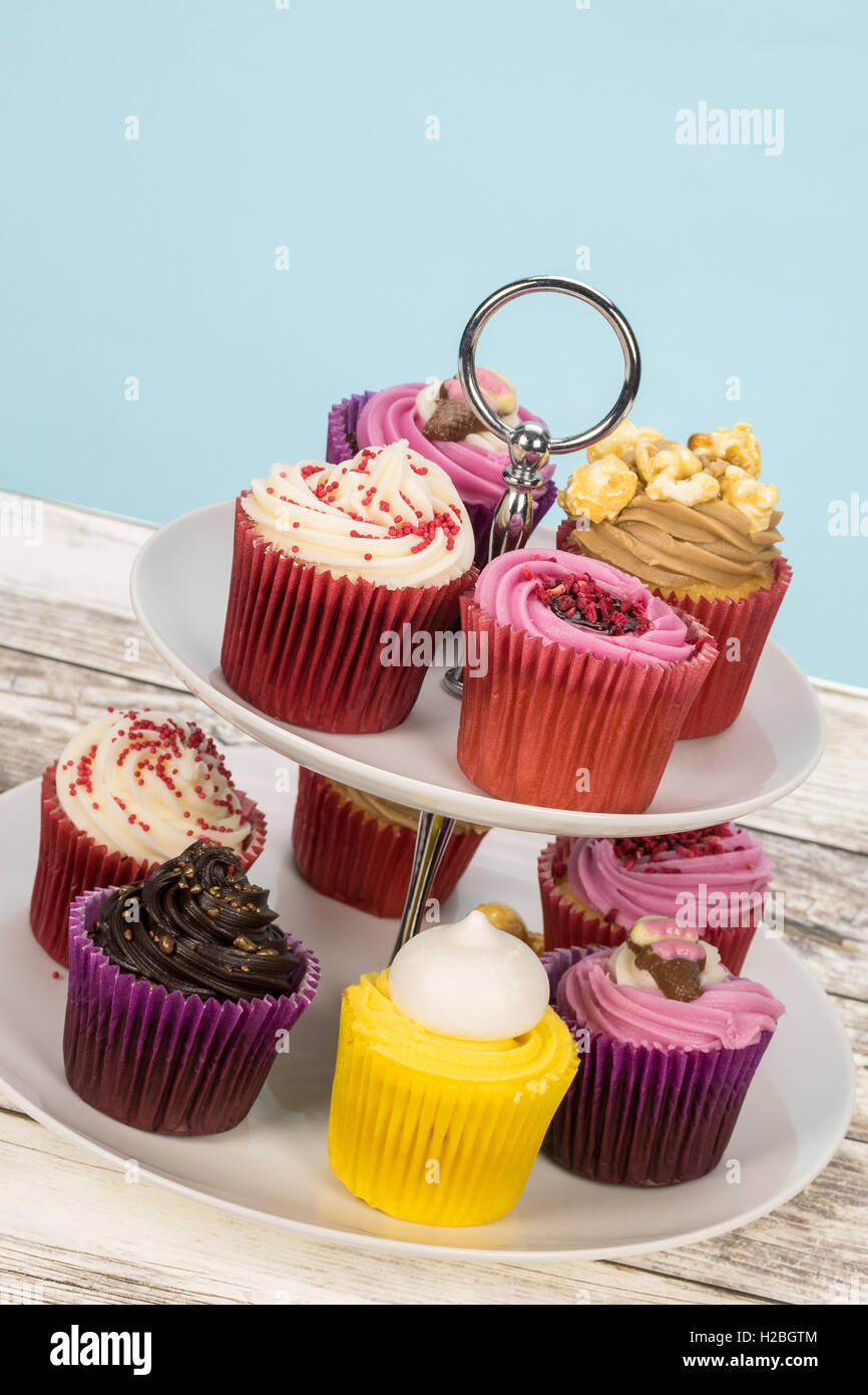 An assortment of decorated cupcakes on a cake stand - tilted shot - Stock Image