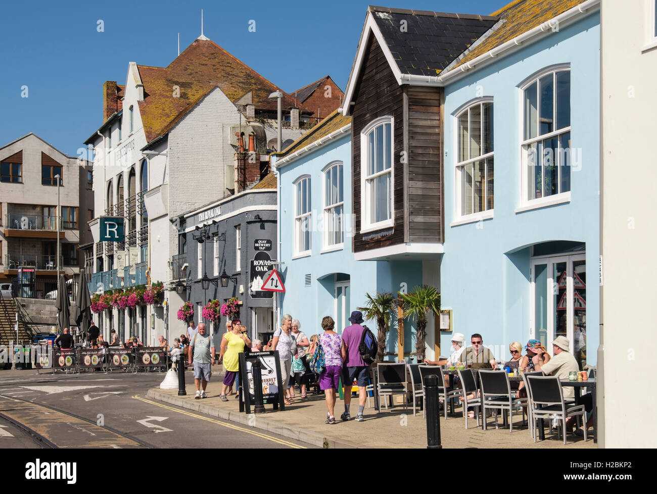 People dining outside The Ship Inn and Royal Oak pubs in September sunshine. Custom House Quay, Weymouth, Dorset, - Stock Image