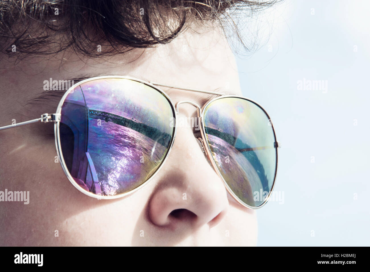 Young caucasian boy with mirroring bridge in sunglasses. Summer theme. Youngster portrait. Stock Photo