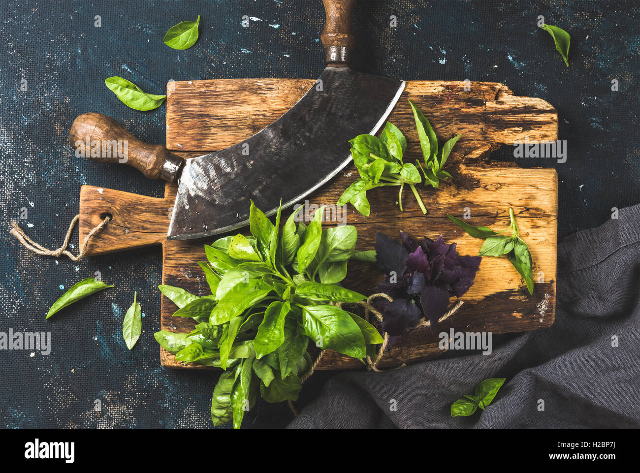 Fresh basil and vintage herb chopper on rustic wooden board - Stock Image