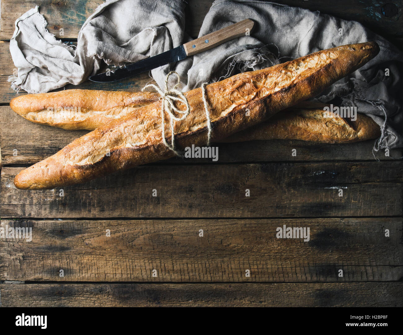 French baguettes on rough rustic wooden background - Stock Image