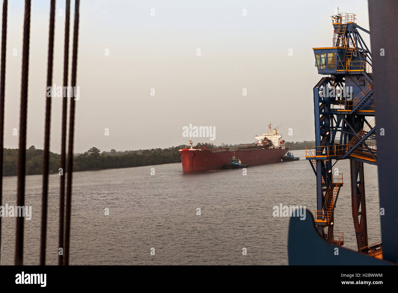 Marine and port operations from jetty. Two tugs moving and turning cargo ship, before vessel moors up and berths - Stock Image