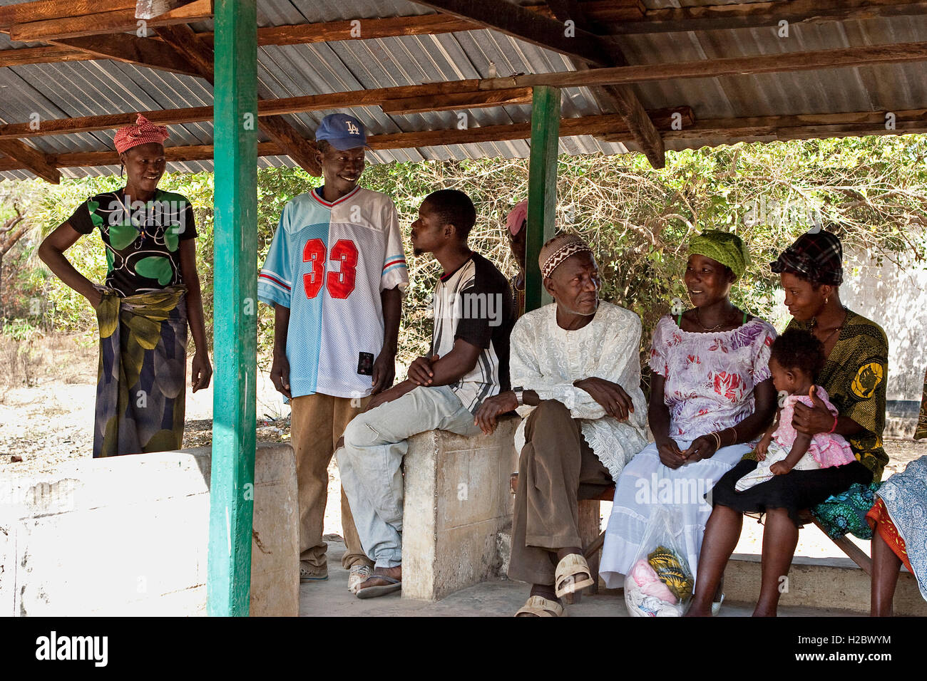 Patients, family and friends waiting outside health clinic, a community project supported by iron ore company in - Stock Image