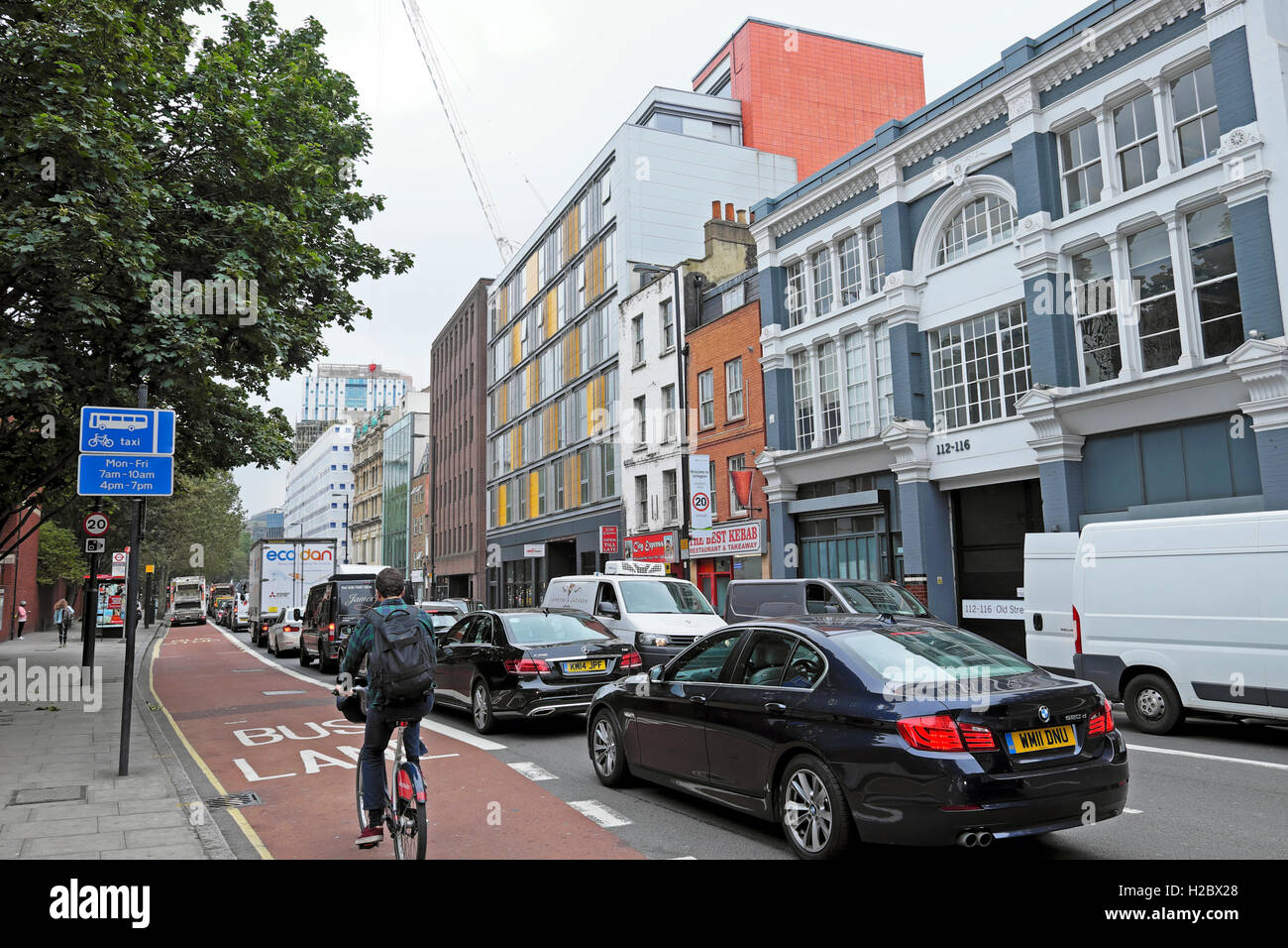 Cyclist in bicycle lane amidst car traffic on Old Street cycling towards Silicon Roundabout in London E1  KATHY - Stock Image