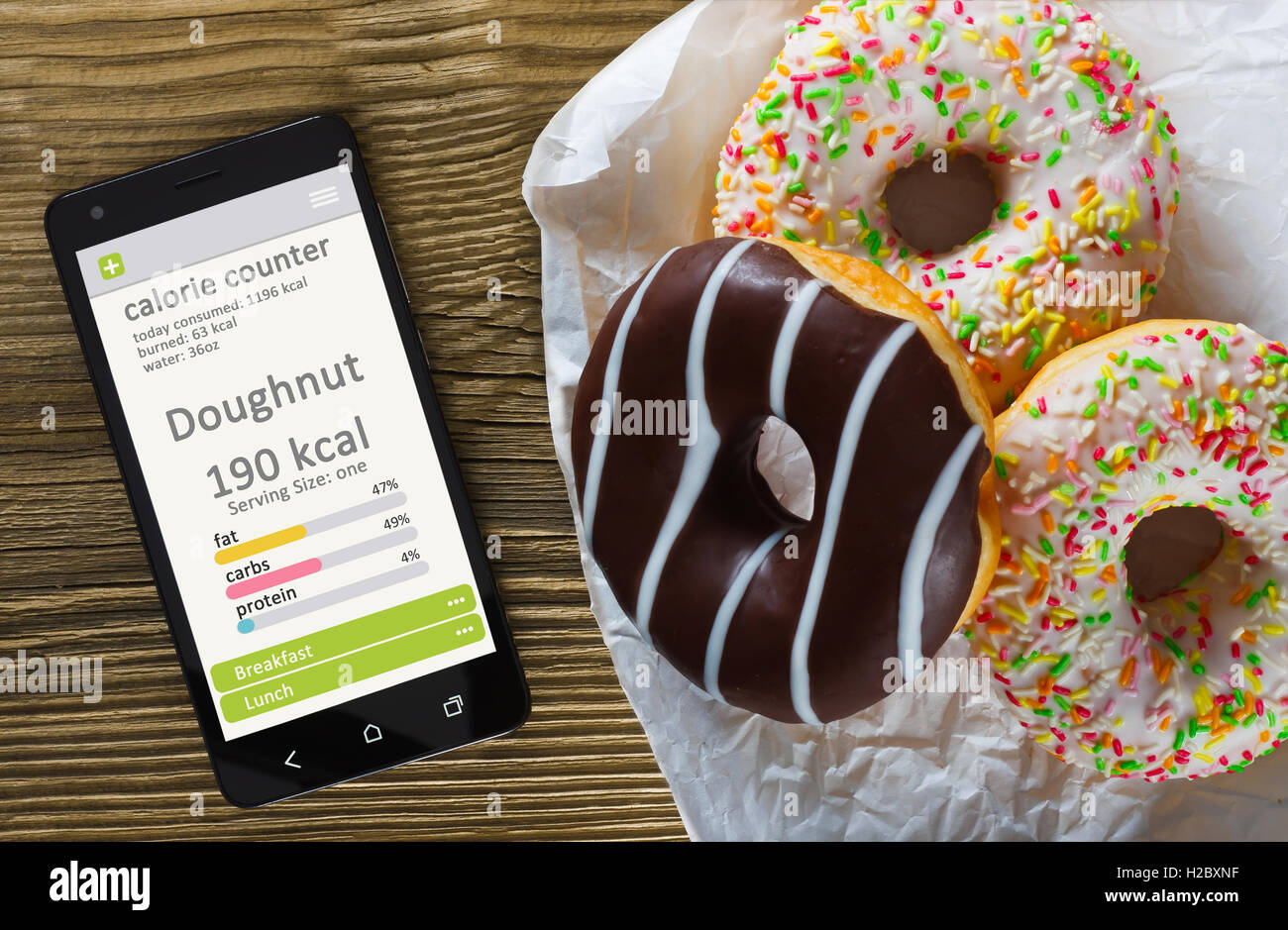 Calorie counter concept - mobile phone with calorie counter app on the screen and doughnuts. Wooden table as background - Stock Image